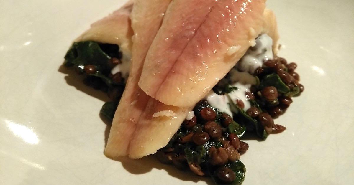 Bio-Forelle auf Belugalinsen und Blattspinat mit Joghurt-Dip. Gesunde Vorspeise für Gäste und Feste.